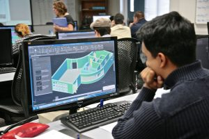 Student designing a house on a computer