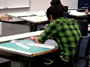student designing in drawing surface desk