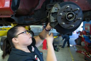student working on a car rotor