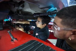 two students working under a car