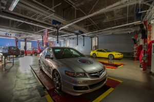 gray car and yellow car in automotive lab