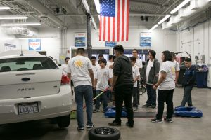 middle school student learning how to change a tire with the help of instructor