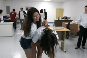 student applying the Heimlich maneuver to another student