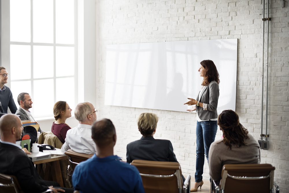 Woman speaking to small group in front of a whiteboard