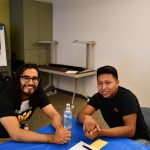 Angel Aguilar Garcia, Mentor, & Donaldo Chun, mentee. Sitting at a table and smiling for the camera.