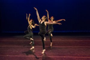 Dancers stand on one leg and reach towards stage right