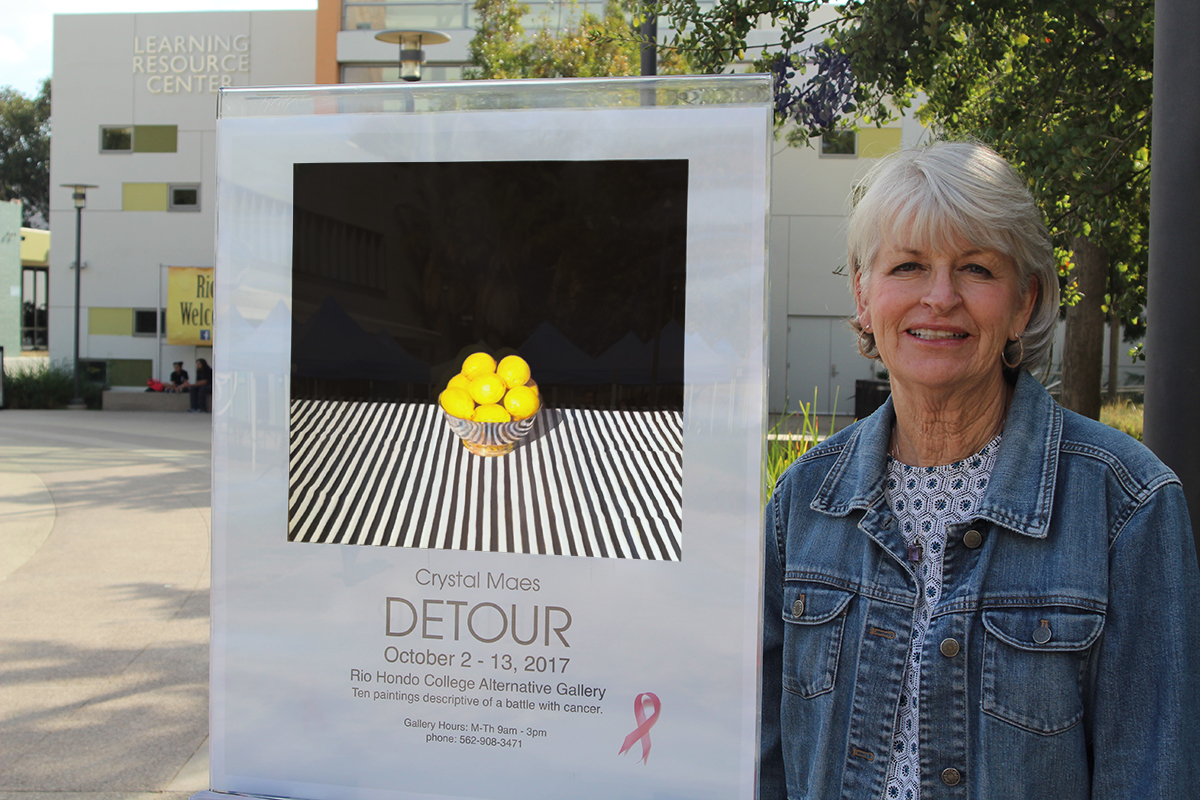 Crystal Maes standing next to her art exhibit poster