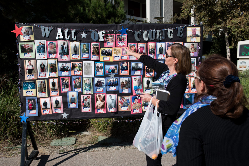"""Rose Sanceda, center, points to a photo of her son Vic Sanceda, currently serving in the USMC, on the """"Wall of Courage"""" after a special ceremony at Rio Hondo College on Wednesday, Nov. 8, 2017. The ceremony honored alumni veterans with a color guard, presentation of commemoration coins, and a speech from two military veterans. (Michael Ares for the Whittier Daily News/SCNG)"""